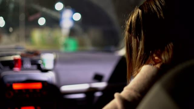 giovane donna entra in auto e ribalta la cintura di sicurezza - imbarcarsi video stock e b–roll
