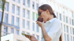 Young woman enthusiastically texting phone and eating muffin outdoors