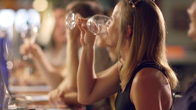 vídeos y material grabado en eventos de stock de young woman excitedly sips a glass of white wine during a taste-testing event at a winery. - catavinos