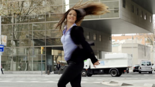 Young woman executive dancing in the street.