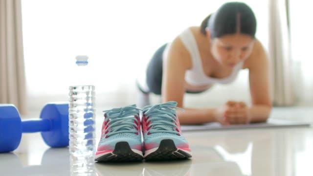 vídeos de stock, filmes e b-roll de corpo de jovem mulher exercício núcleo por prancha - tatame equipamento para exercícios