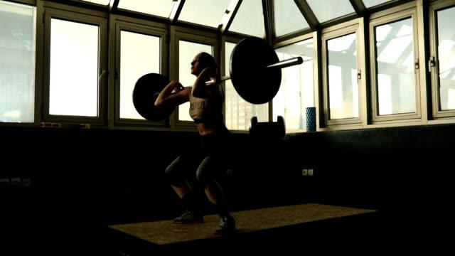 vídeos de stock, filmes e b-roll de exercício de mulher jovem com peso no ginásio - treino cruzado