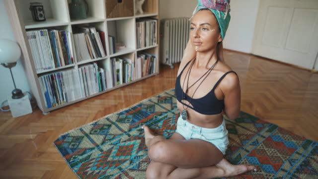 stockvideo's en b-roll-footage met jonge vrouw die en yoga thuis uitoefent en doet - op de grond zitten
