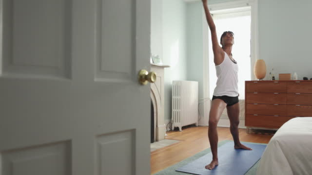 WS Young woman exercising in bedroom / Brooklyn, New York City, USA