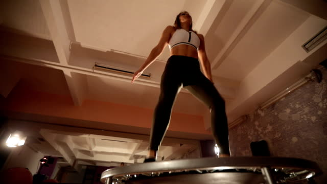 young woman exercising on a mini-trampoline - cardiovascular exercise stock videos & royalty-free footage