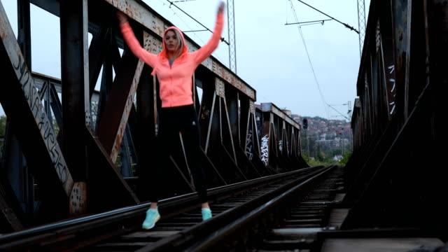 Young woman exercising on railway bridge