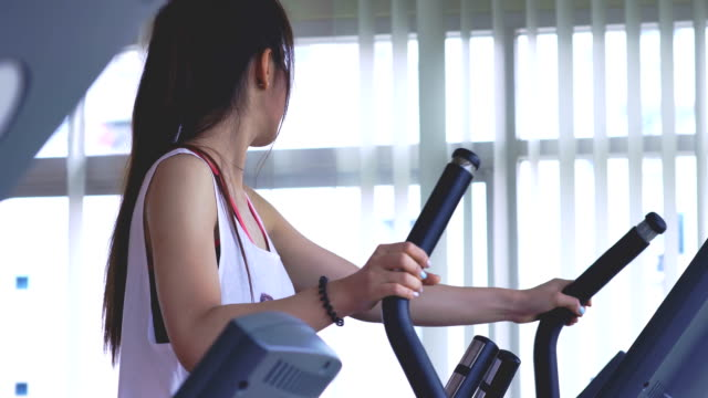 young woman exercising on the cross trainer machine - cross trainer stock videos & royalty-free footage