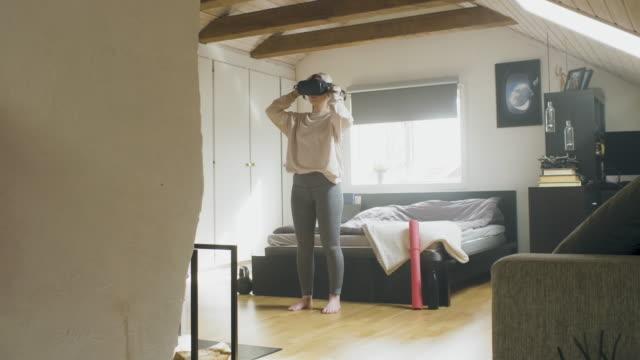 vidéos et rushes de jeune femme faisant l'exercice avec un casque de vr à la maison - une seule jeune femme