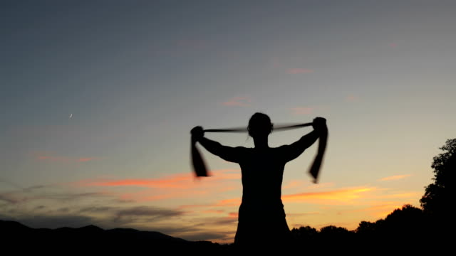 Young Woman Exercising With Resistance Band Outdoors After Sunset