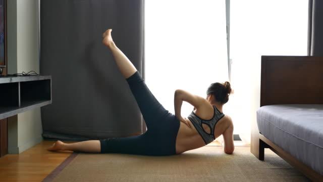 vídeos de stock, filmes e b-roll de young woman exercício yoga na sala de estar em casa - boa postura