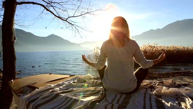 young woman exercising yoga by the lake at sunset - lotus position stock videos & royalty-free footage