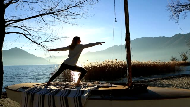 young woman exercising yoga by the lake at sunset - balance stock videos and b-roll footage