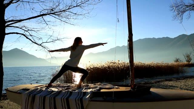 junge frau, die ausübung von yoga am see bei sonnenuntergang - gleichgewicht stock-videos und b-roll-filmmaterial