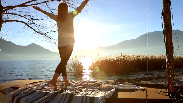 Young woman exercising yoga by the lake