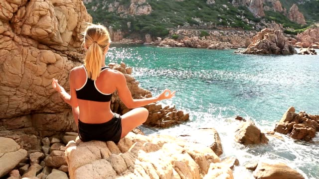 Young woman exercising yoga by the sea