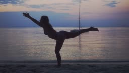 Young woman exercising yoga, doing pose on beach during beautiful sunset. slow motion. 1920x1080