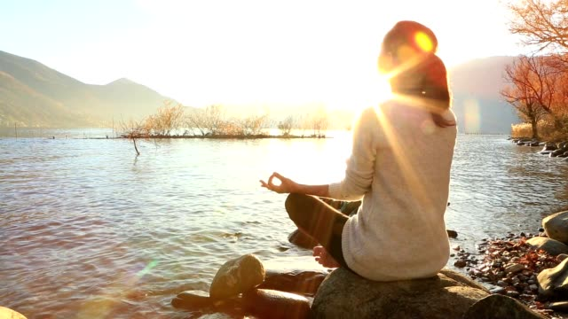 Junge Frau Ausübung yoga-Bewegungen bei Sonnenaufgang