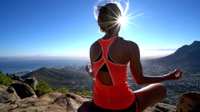 Young woman exercising yoga on mountain top