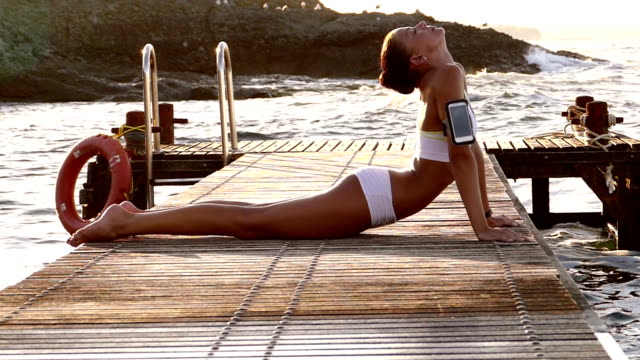 young woman exercising yoga on the quay slow motion - one young woman only stock videos & royalty-free footage