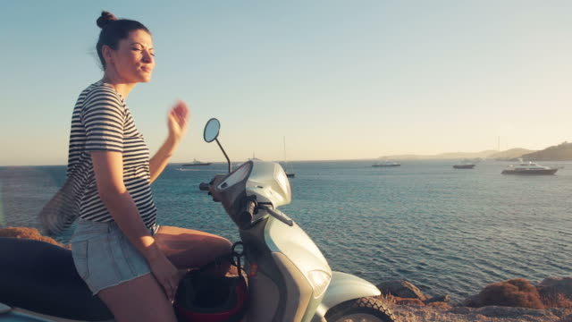Young woman experiencing freedom at sunset on the motor scooter.