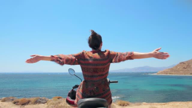 Junge Frau, die Freiheit auf dem Motorroller am Meer zu erleben.