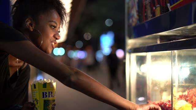 vídeos de stock e filmes b-roll de young woman experiencing local food in the street at night - feirante