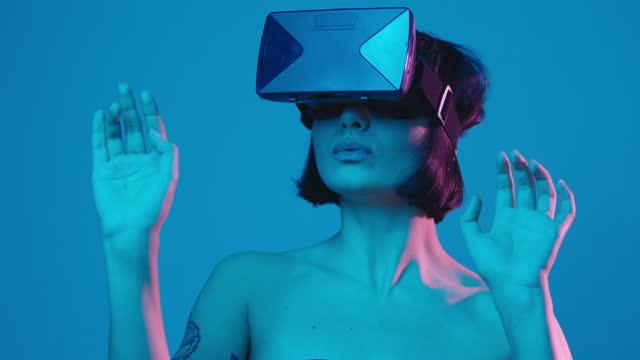 junge frau erlebt virtuelle realität durch ein vr-headset isoliert auf blauem neon-copyspace - schutzbrille stock-videos und b-roll-filmmaterial