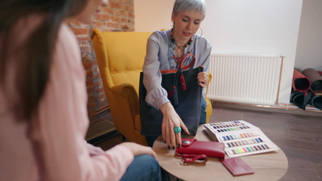 young woman explaining design options for bags and wallets to her customer - strategia di vendita video stock e b–roll