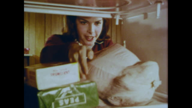 1966 young woman explains that her turkey is usda grade a as she places it in the fridge - label stock videos & royalty-free footage