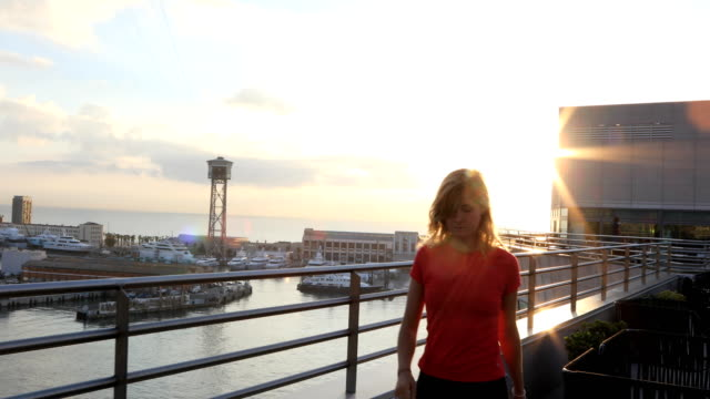 young woman explores seafront harbour area of city at sunrise, barcelona - stuhl stock-videos und b-roll-filmmaterial