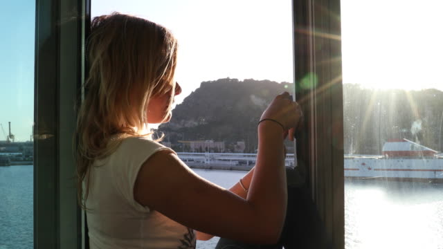 young woman explores seafront harbour area of city, barcelona - window frame stock videos and b-roll footage