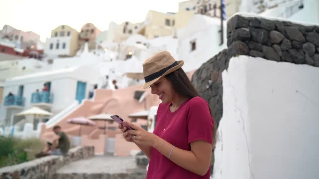 young woman exploring and using mobilepone during vacations in greek island - santorini stock videos & royalty-free footage