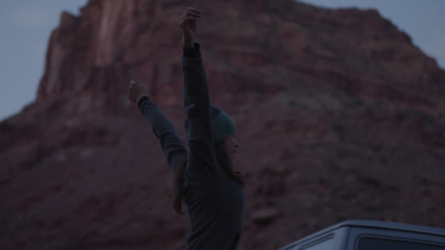 vídeos de stock e filmes b-roll de young woman exploring moab stretches after sleeping in vehicle overnight. - acordar