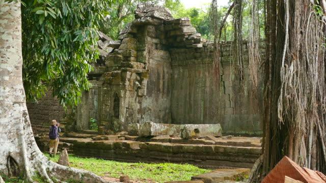 Mujer joven explorar ruina de Angkor templo en Camboya