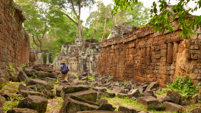 young woman exploring old ruin of angkor temple in cambodia - circa 12th century stock videos and b-roll footage