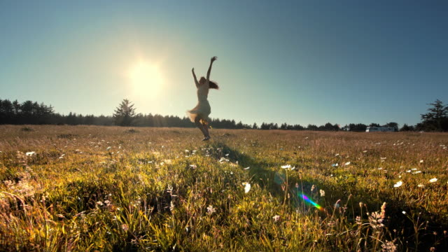 Young woman expressing joy in field of flowers, Oregon