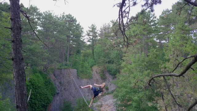 a young woman falls while slacklining on a tightrope. - tightrope stock videos & royalty-free footage