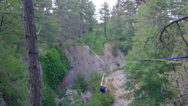 stockvideo's en b-roll-footage met a young woman falls while slacklining on a tightrope. - trust