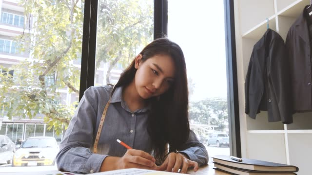 若い女性のファッションデザイナーのデザインとスケッチは、測定テープで服をドレッシングと生地の色のスウォッチを使用していますパントンと衣料デザインスタジオ - 生地サンプル点の映像素材/bロール