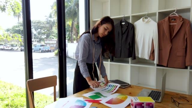 若い女性のファッションデザイナーのデザインとカラースウォッチとドレッシング服のスウォッチファブリックカラー衣料デザインスタジオでパントン - トルソー点の映像素材/bロール