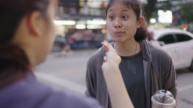 vidéos et rushes de jeune femme alimentant la nourriture à un ami. nourriture de rue thaïlandaise. - content