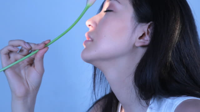 CU Young woman feeling and playing with calla lily flower / New York, New York, USA