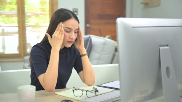 vidéos et rushes de jeune femme se sentant stressé et fatigué de travailler pour la réunion de conférence vdo avec l'équipe dans ma maison, le travail de la maison après l'éclosion du virus covid-19, et la distanciation sociale. - after work
