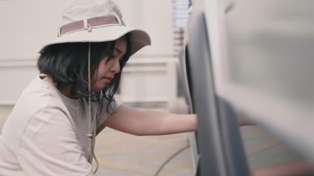 若い女性の車のタイヤに空気を充填します。 - touching点の映像素材/bロール