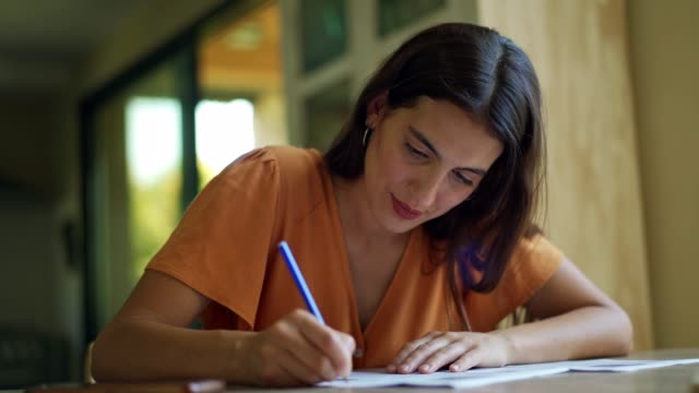 young woman filling in paperwork - note message stock videos & royalty-free footage
