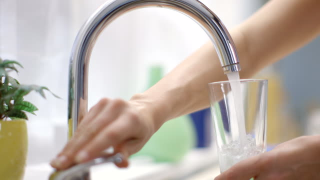 Young woman fills glass under running tap in kitchen.