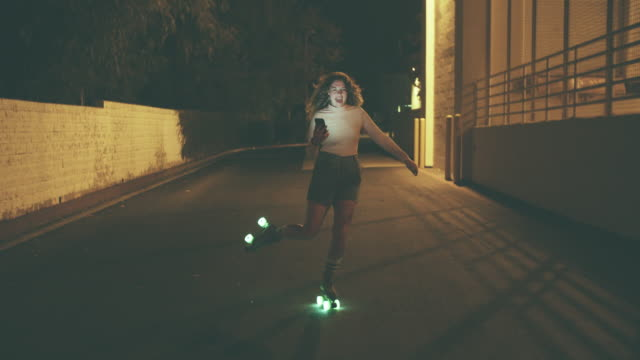 vídeos de stock e filmes b-roll de young woman filming herself on roller skates at night - funky