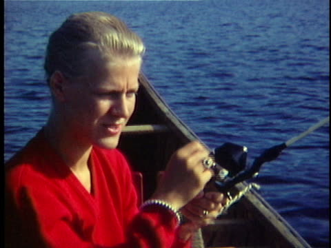 1965 CU Young woman fishing from canoe in Lake Edward, Quebec, Canada
