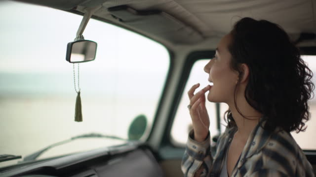 cu young woman fixing her make up in camper van - 付ける点の映像素材/bロール