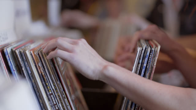 vídeos de stock e filmes b-roll de young woman flips through vinyl records looking for bargains in austin music shop - escolha